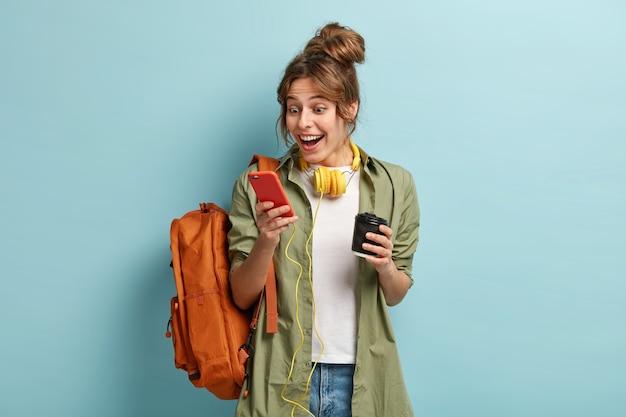 Bild des lächelnden freudigen weiblichen teenagers genießt kommunikation mit freund im gruppenchat, sieht lustige fotos online an, hört musik offline mit kopfhörern, trinkt aromatischen kaffee aus pappbecher