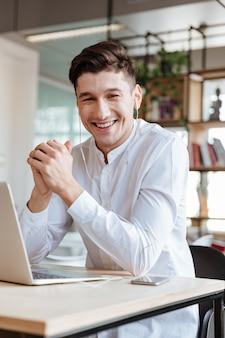 Bild des lächelnden mannes, der in weißem hemd gekleidet wird und laptop-computer benutzt, während er musik hört. coworking. schauen sie in die kamera.