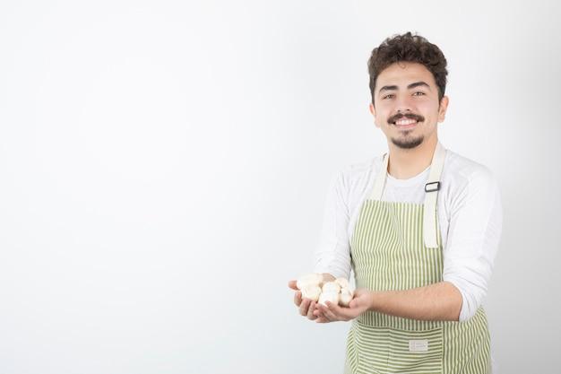 Bild des männlichen kochs, der rohe pilze auf weiß hält
