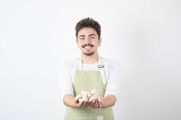 Bild des männlichen kochs, der rohe pilze mit glücklichem ausdruck auf weiß hält