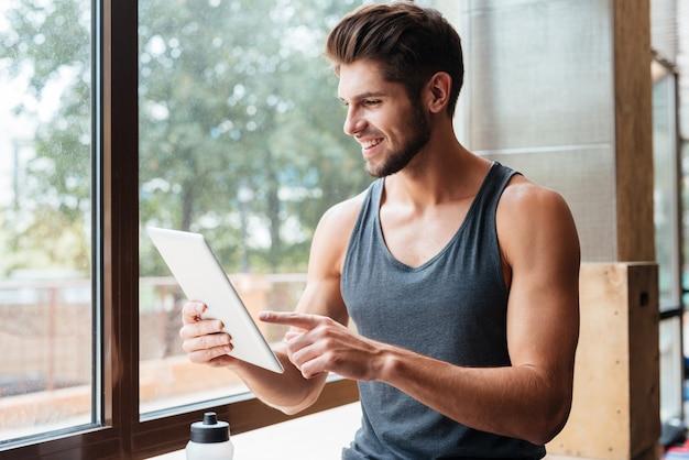 Bild des models im fitnessstudio mit tablet