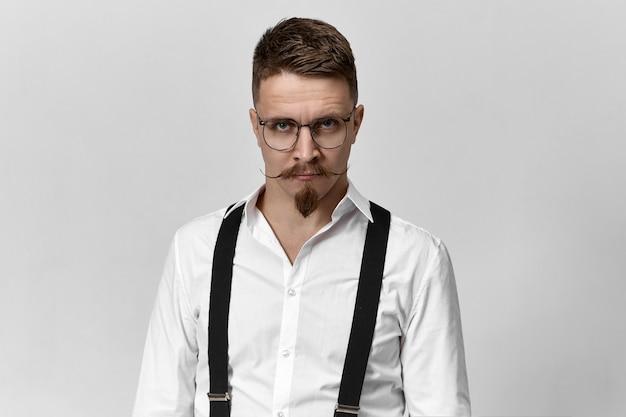 Bild des modischen jungen bärtigen männlichen hochschullehrers, der brillen, hosenträger trägt