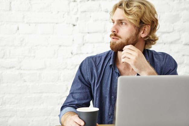 Bild des nachdenklichen ernsten jungen europäischen mannes mit dem dicken bart, der am kaffeehaus entspannt, morgencappuccino genießt, vor offenem laptopcomputer während des frühstücks sitzt und nachrichten liest