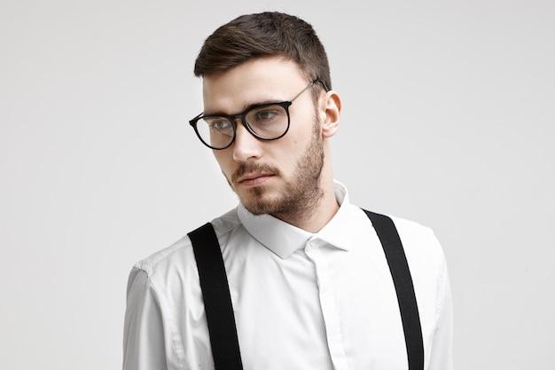 Bild des nachdenklichen gut aussehenden jungen kaukasischen geschäftsmannes mit beschnittenem bart und schnurrbart, die an der weißen bürowand stehen und ernstes nachdenkliches aussehen haben. geschäfts-, stil- und erfolgskonzept