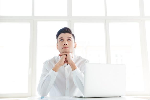 Bild des nachdenklichen mannes im weißen hemd mit laptop-computer gekleidet. coworking.