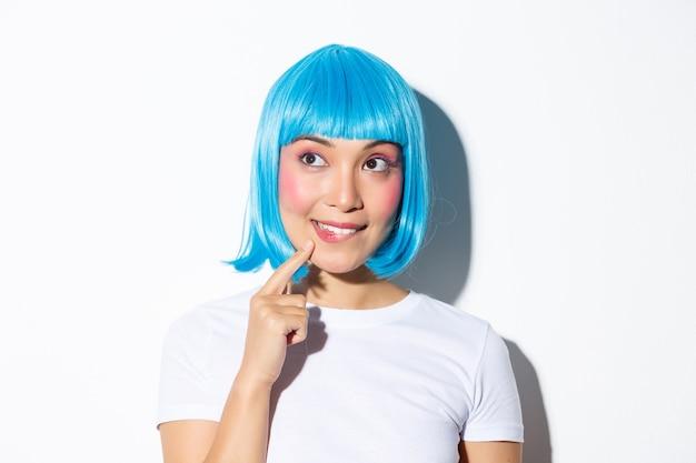 Bild des nachdenklichen niedlichen asiatischen mädchens in der blauen perücke, die obere linke ecke betrachtend und denkend stehend.