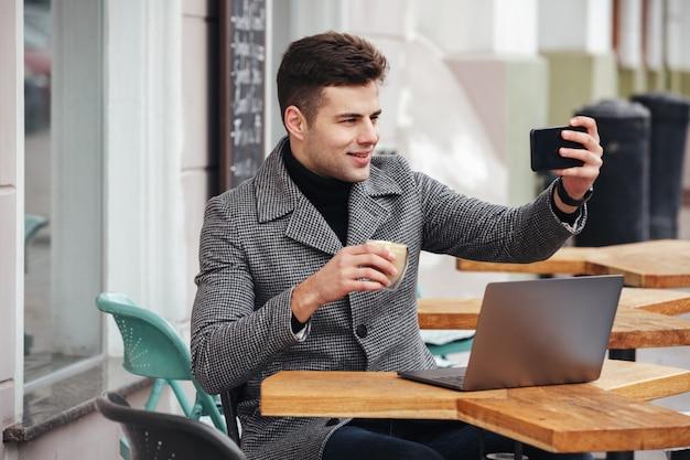 Bild des netten brunettemannes, der selfie oder das skyping beim stillstehen im straßencafé macht und kaffee vom glas trinkt