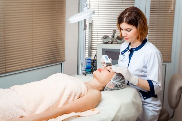 Bild des netten kosmetikers sauerstofftherapie für das legen der jungen frau tuend