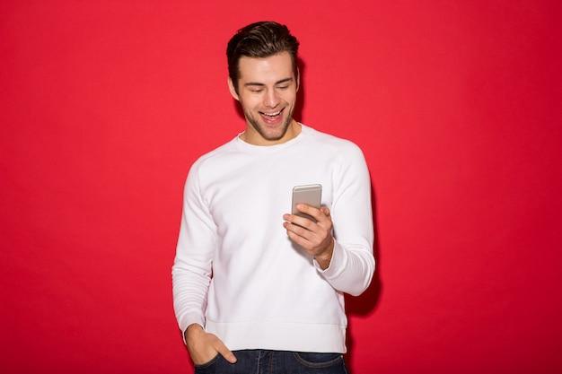 Bild des netten mannes in der strickjacke unter verwendung des smartphone über roter wand