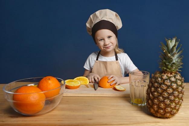 Bild des niedlichen blonden 7-jährigen jungen in der kochuniform, die am hölzernen küchentisch steht