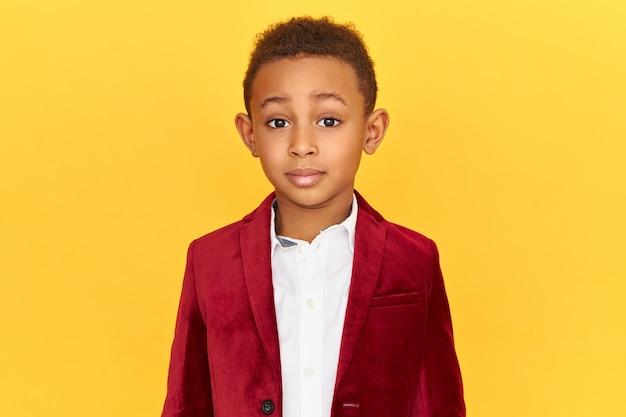 Bild des niedlichen charmanten kleinen afroamerikanischen jungen, der stilvolle kleidung trägt, die isoliert betrachtet kamera in der faszination aufwirft, erstaunt mit großen verkaufspreisen
