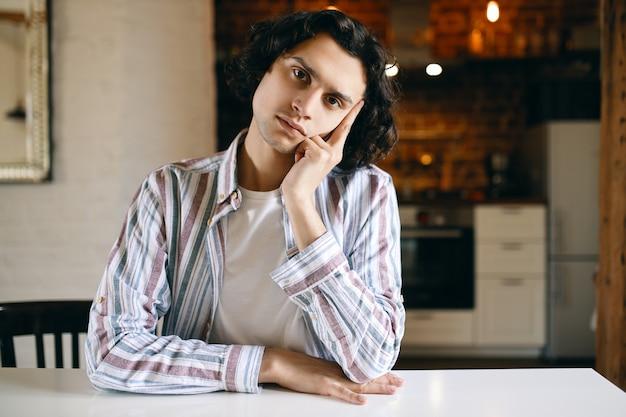 Bild des niedlichen kerls in der freizeitkleidung mit gelangweiltem gesichtsausdruck, desinteressiert, am tisch sitzend