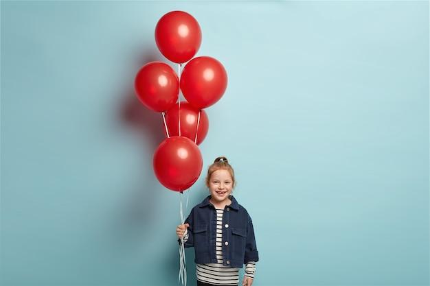 Bild des niedlichen kleinen kindes in der modischen jeansjacke steht mit roten luftballons, kommt am geburtstag des freundes, hat glücklichen gesichtsausdruck, steht über blauer wand. kindheits- und feierkonzept