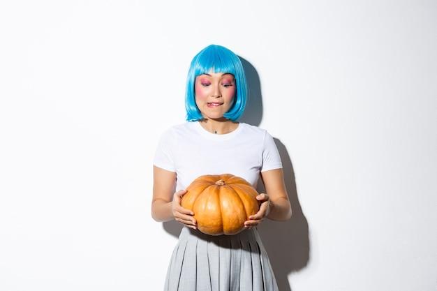 Bild des niedlichen mädchens, das kürbis für halloween auswählt, blaue perücke tragend, stehend.