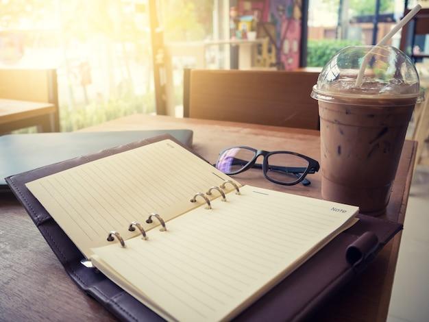 Bild des offenen notizbuches mit eiskaffee und gläser und laptop auf holztisch.