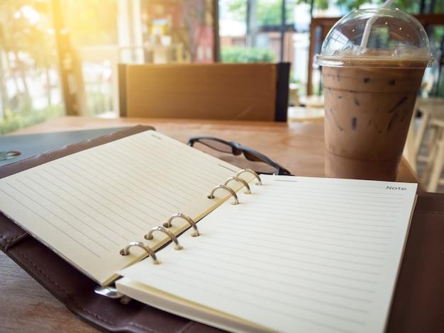 Bild des offenen notizbuches mit eiskaffee und -gläsern auf holztisch.