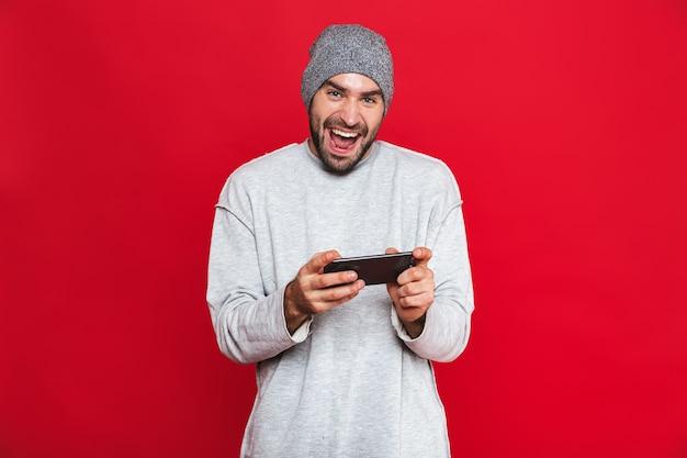 Bild des optimistischen mannes 30s, der smartphone hält und videospiele spielt, lokalisiert