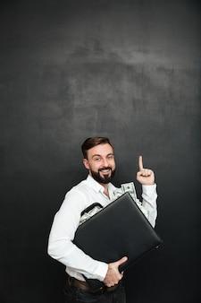 Bild des optimistischen mannes seinen preis freuend, der schwarzen aktenkoffer mit vielen bargelddollar nach innen, aufwärts lokalisiert über dunkelgrau zeigend umarmt
