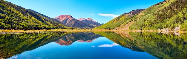 Bild des panoramas des sees in den bergen, umgeben von herbstbäumen und roten sandigen berggipfeln