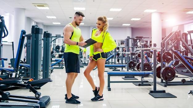 Bild des persönlichen fitnesstrainers und des weiblichen klienten im fitnessstudio, das vor der kamera aufwirft.