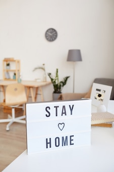Bild des plakats mit text bleiben sie zu hause im wohnzimmer zu hause