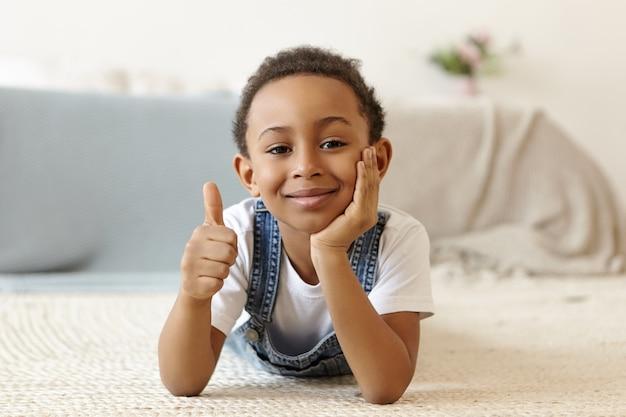 Bild des positiv freundlich aussehenden achtjährigen afroamerikanischen jungen, der zu hause auf dem boden liegt