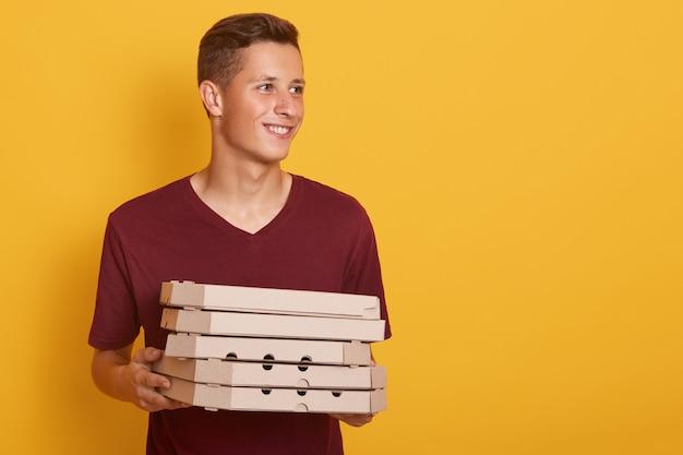 Bild des positiven energetischen jungen, der lässiges rotes t-shirt trägt, pizzaschachteln aus pappe in beiden händen hält, beiseite schaut, aufrichtig lächelt, in guter stimmung ist. copyspace für werbung.