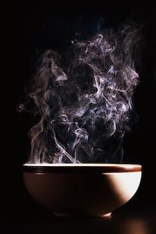 Bild des rauches, der vom essen über der tasse steigt