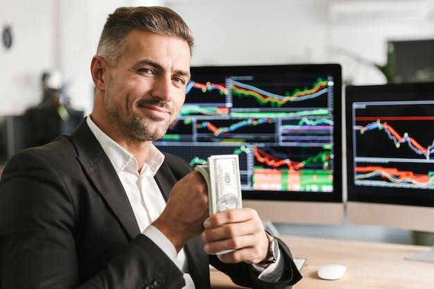 Bild des reichen geschäftsmannes der 30er jahre, der anzug hält, der pack des geldes hält, während im büro mit grafiken und diagrammen auf computer arbeitet