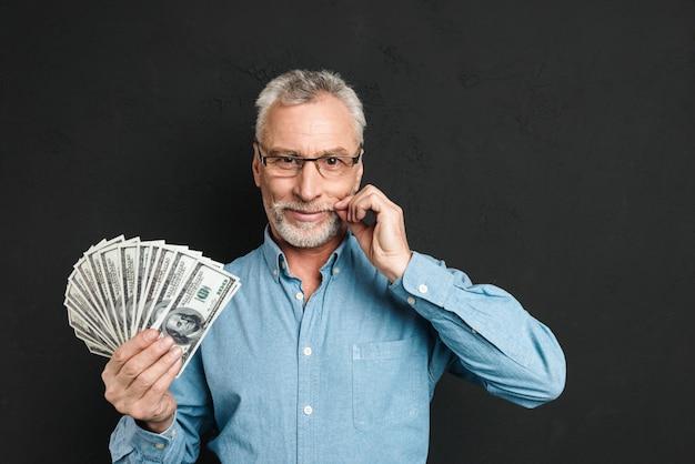 Bild des reichen mannes mittleren alters der 60er jahre mit grauem haar, das geldfan von 100-dollar-scheinen hält und seinen grauen schnurrbart berührt, lokalisiert über schwarzer wand