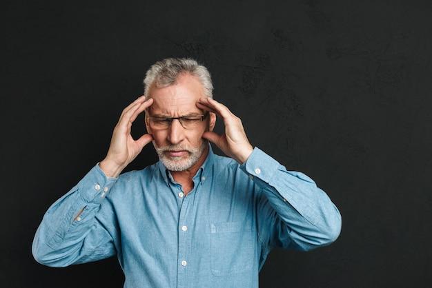 Bild des reifen mannes 60s mit grauem haar und bart, der unter migräne leidet und schläfen aufgrund von kopfschmerzen reibt, isoliert über schwarzer wand