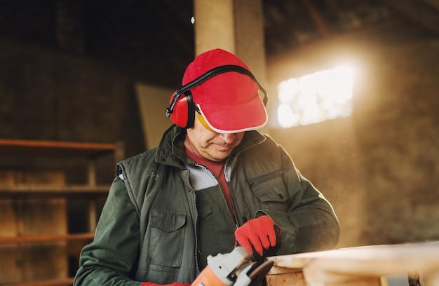 Bild des reifen zimmermannsmannes in der schutzuniform, die holz mit elektrischem schleifer formt. an einem sonnigen tag seinen job in seiner arbeitsgarage genießen.