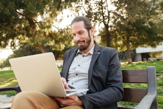 Bild des sachlichen gutaussehenden mannes mit gebundenem haar, das auf silbernem laptop arbeitet, während auf bank im stadtpark während des sonnigen tages sitzend