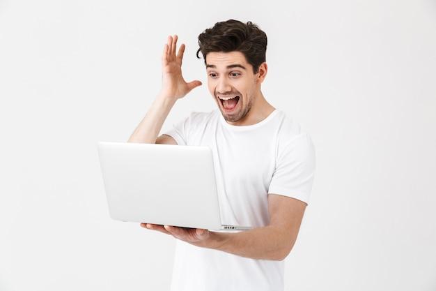 Bild des schockierten aufgeregten jungen mannes, der isoliert über der weißen wand posiert, die laptop-computer verwendet.