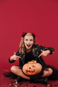 Bild des schockierten positiven kleinen mädchenteufels im karnevals-halloween-kostüm