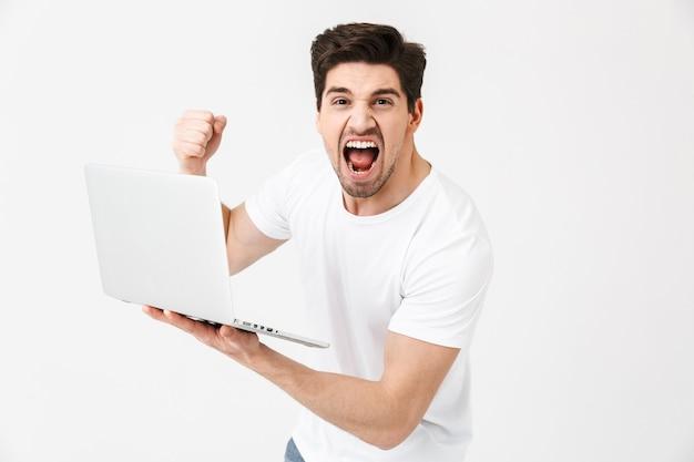 Bild des schockierten schreienden jungen mannes, der isoliert über der weißen wand mit laptop-computer posiert.