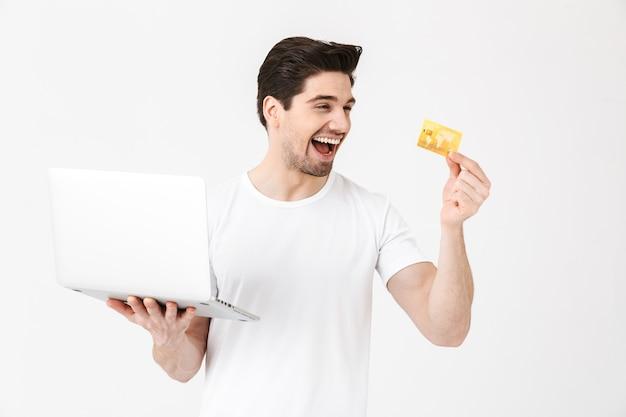 Bild des schockierten, schreienden jungen mannes, der isoliert über der weißen wand posiert und den laptop-computer mit kreditkarte verwendet.