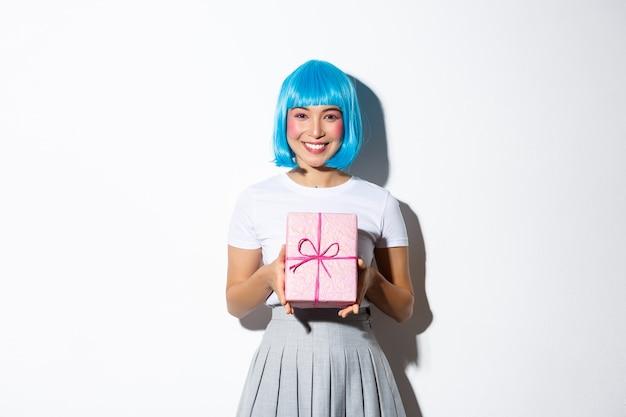 Bild des schönen asiatischen mädchens in der blauen parteiperücke, die mit feiertag gratuliert, geschenk hält und lächelt, stehend.