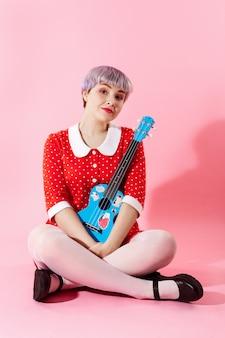 Bild des schönen dollischen mädchens mit dem kurzen hellvioletten haar, das rotes kleid trägt, das blaue ukulele über rosa wand hält