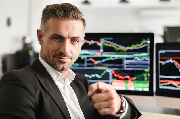 Bild des schönen geschäftsmanns 30s tragen anzug, der im büro am computer mit grafiken und diagrammen am bildschirm arbeitet