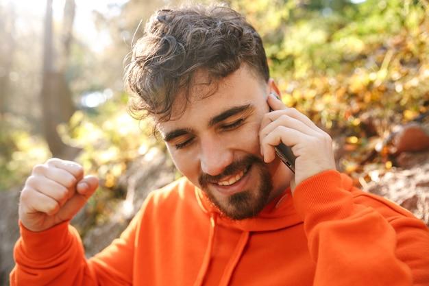 Bild des schönen glücklichen jungen sportfitnessmannläufers draußen im park, der durch handy spricht.