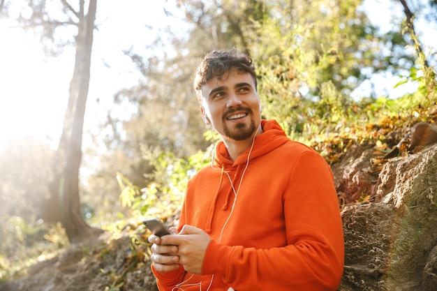 Bild des schönen glücklichen jungen sportfitnessmannläufers draußen im park, der musik mit kopfhörern unter verwendung des mobiltelefons hört.