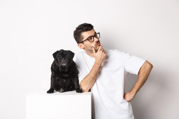 Bild des schönen jungen mannes, tierhalter, der mit seinem hund steht und direkt auf logo schaut, posiert mit mops gegen weiß