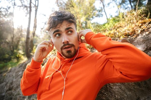 Bild des schönen jungen sportfitnessmannläufers draußen im park, der musik mit kopfhörern hört.