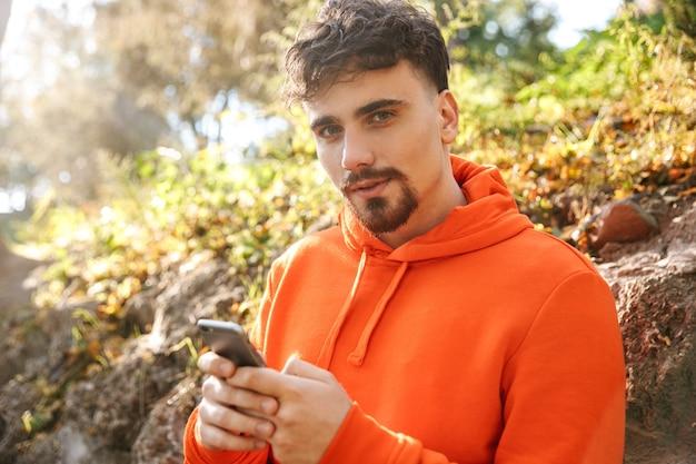 Bild des schönen jungen sportfitnessmannläufers draußen im park unter verwendung des mobiltelefons.