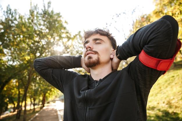 Bild des schönen jungen sportfitnessmannläufers draußen im park.