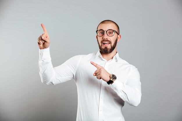 Bild des schönen kaukasischen mannes im weißen hemd und in den brillen, die auf kamera aufwerfen und finger nach oben auf kopienraum zeigen, lokalisiert über graue wand
