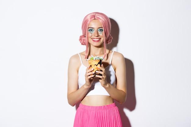 Bild des schönen lächelnden mädchens in der rosa perücke, die süßes oder saures süßigkeiten hält, halloween feiert, stehend.
