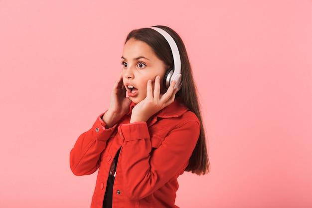 Bild des schönen schockierten kleinen mädchens, das musik mit kopfhörern lokalisiert über rosa wand hört.
