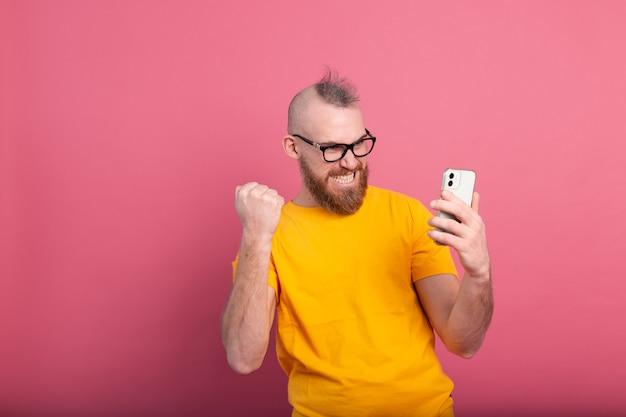 Bild des schreienden jungen bärtigen gutaussehenden mannes, der sieg und erfolg sehr aufgeregt auf rosa feiert